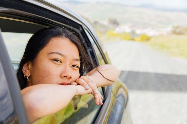 Jeune, femme asiatique, regarder dehors, fenêtre machine Photo gratuit