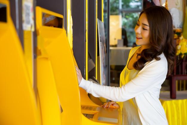 Jeune Femme Asiatique, Retirer De L'argent Avec Une Carte à La Machine Automatique, Femme Debout Au Guichet Automatique De La Banque Photo Premium