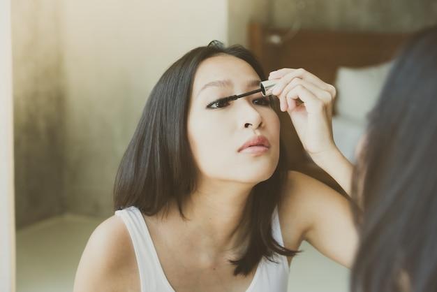 Jeune femme asiatique se maquiller Photo gratuit