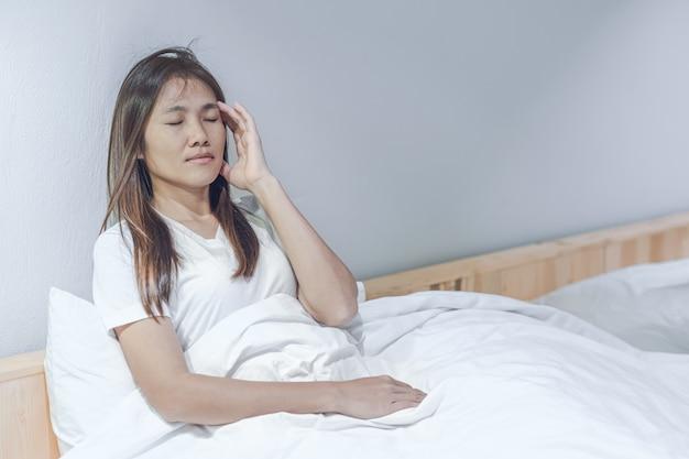 Jeune femme asiatique se sentant mal à la tête et malaise sur un lit blanc dans sa chambre. Photo Premium