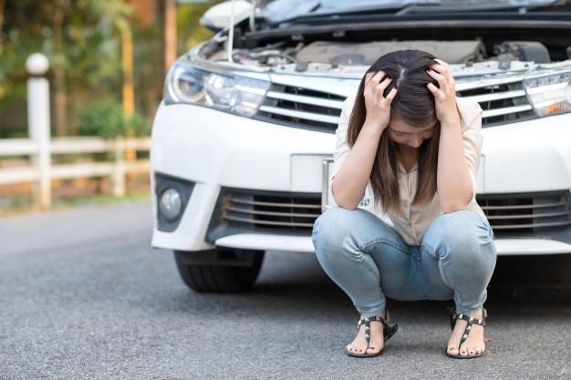 Jeune femme asiatique se sentir triste assis près de la voiture en panne Photo Premium