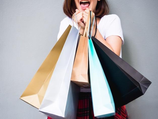 Jeune femme asiatique shopping heureux d'été avec des sacs sur fond gris à l'espace de copie Photo gratuit
