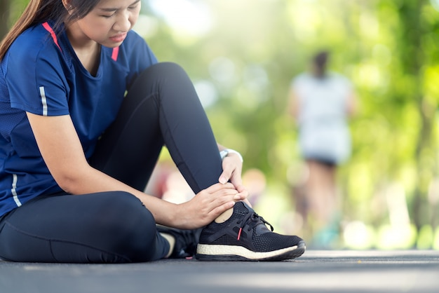 Jeune femme asiatique souffrant d'une blessure à la cheville. Photo Premium