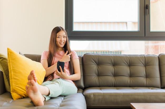 Jeune Femme Asiatique Souriant Joyeusement, Se Sentant Heureux Et Pointant Vers Le Côté Et Vers Le Haut, Montrant L'objet Dans L'espace De Copie Photo Premium