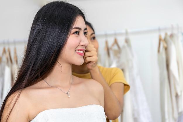 Jeune Femme Asiatique Souriante Et Essayant La Robe De Mariée Dans Un Magasin. Photo Premium