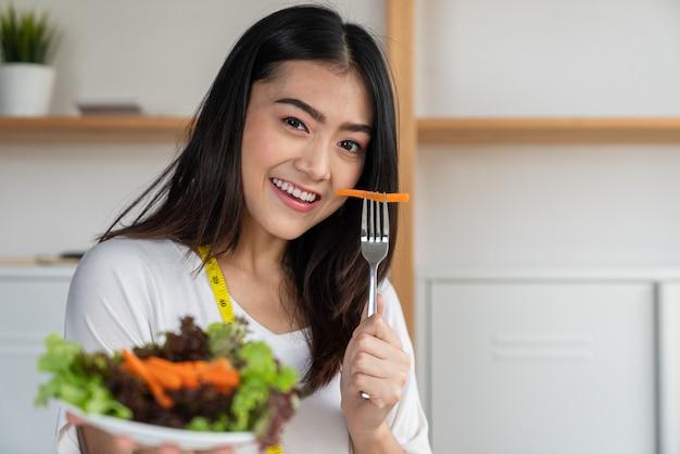 Jeune femme asiatique souriante perdre du poids, manger de la salade de légumes dans les plats sur sa main, un régime et un concept de bonne santé Photo Premium