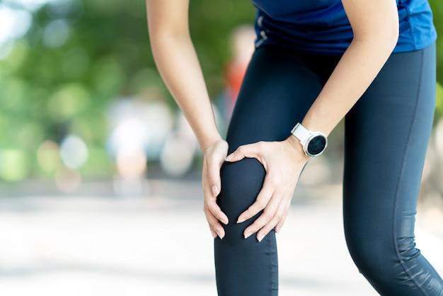 Jeune femme asiatique tenant une douleur au genou dans un parc naturel public Photo Premium