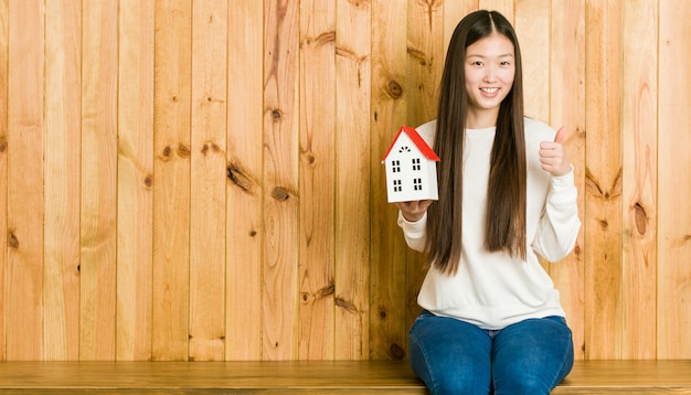 Jeune femme asiatique tenant une icône de la maison souriante et levant le pouce vers le haut Photo Premium