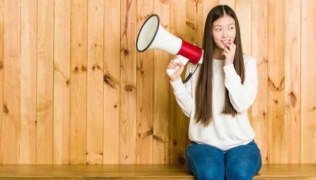 Jeune Femme Asiatique Tenant Un Mégaphone Détendu Pensant à Quelque Chose En Regardant Un Espace De Copie. Photo Premium