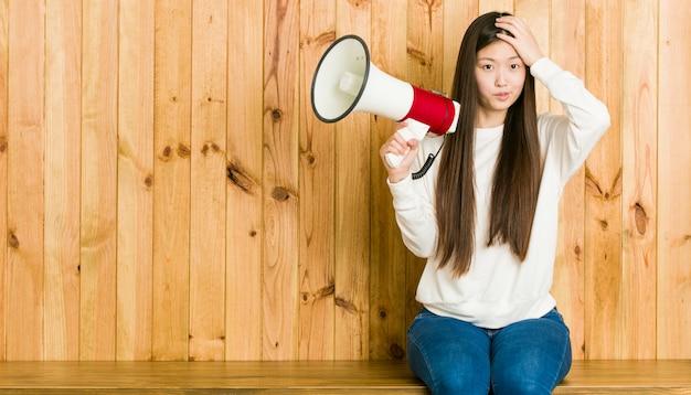 Jeune Femme Asiatique Tenant Un Mégaphone Sous Le Choc, Elle S'est Souvenue D'une Réunion Importante. Photo Premium