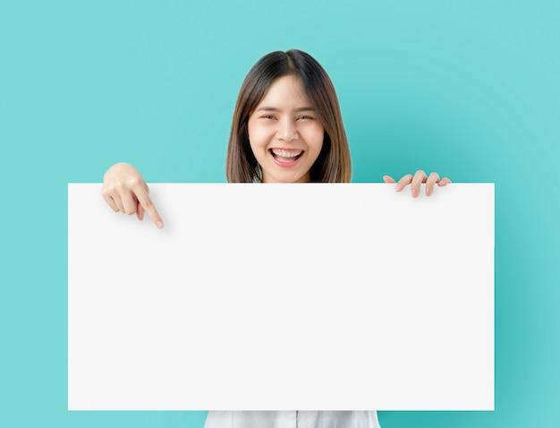 Jeune femme asiatique tenant un papier vierge avec un visage souriant et à la recherche sur le bleu. Photo Premium