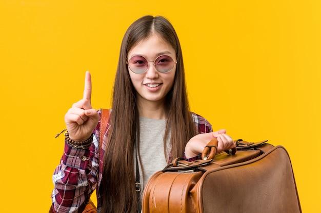 Jeune femme asiatique tenant une valise montrant le numéro un avec le doigt. Photo Premium