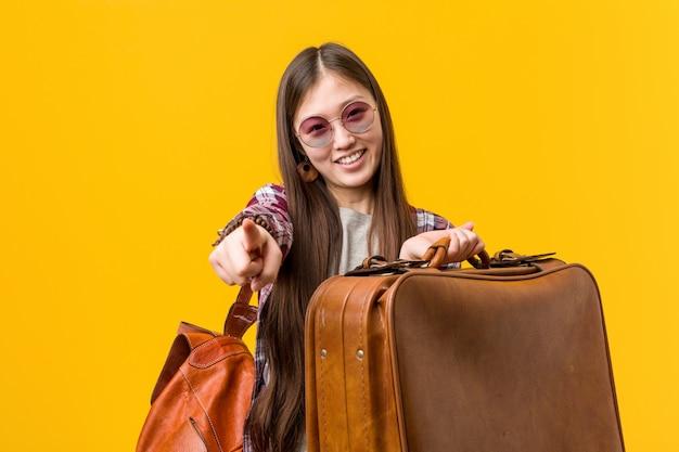 Jeune femme asiatique tenant une valise sourires joyeux pointant vers l'avant. Photo Premium