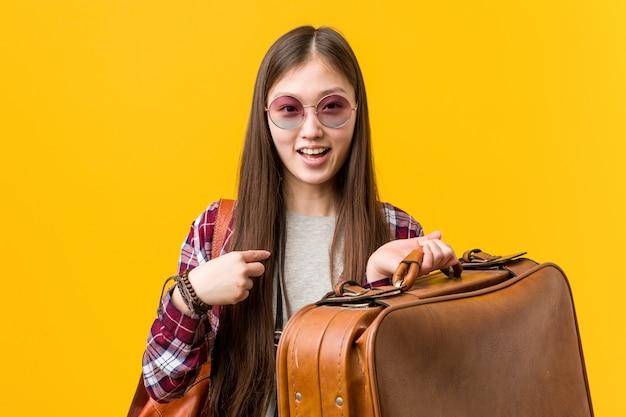 Jeune femme asiatique tenant une valise surprise se montrant du doigt, souriant largement. Photo Premium