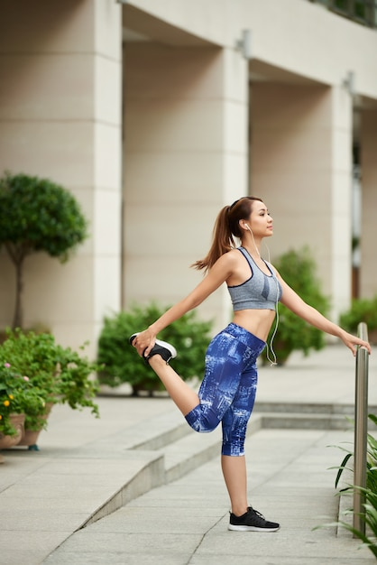 Jeune Femme Asiatique En Tenue De Sport Debout Dans La Rue Et S'étendant Avant L'entraînement Photo gratuit