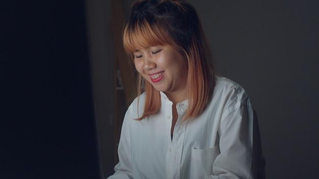 Jeune femme asiatique travaillant tard en utilisant le bureau sur le bureau dans le salon à la maison. Photo gratuit