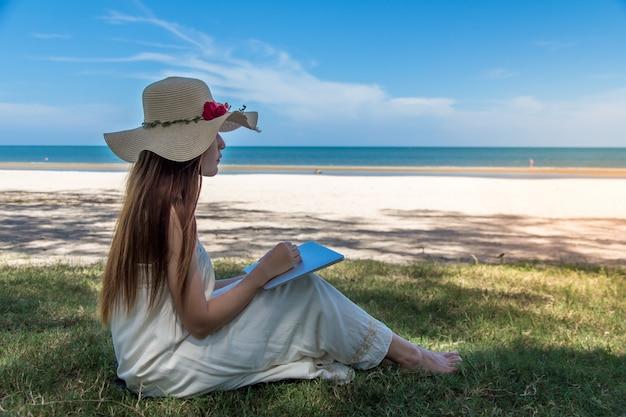 Jeune, femme asiatique, utilisation, ordinateur portable, dans, robe, séance plage Photo Premium