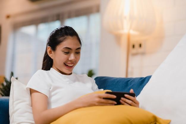 Jeune, femme asiatique, utilisation, smartphone, vérification, médias sociaux, sentir, heureux, sourire Photo gratuit