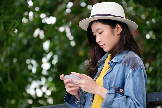 Jeune, femme asiatique, utilisation, téléphone intelligent, dans, dehors, ville, fond, gens, téléphone, style de vie Photo Premium