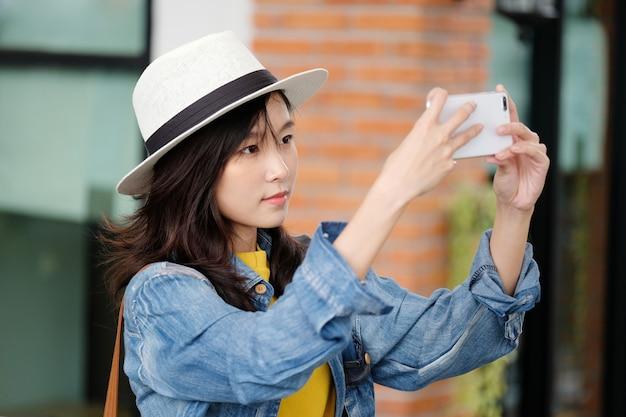 Jeune, femme asiatique, utilisation, téléphone intelligent, dans, ville, dehors, gens, dehors, à, technologie, gens, sur, téléphone, style de vie Photo Premium