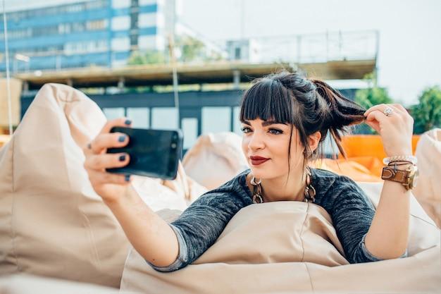 Jeune Femme Assez Confiante, Prendre Une Photo à L'extérieur Dans Une Ville Ou Une Ville Urbaine. Assis Sur Une Chaise Douce Et Prenez Un Selfie. Posant Seul Et Amusez-vous. Vue Urbaine. Photo Premium