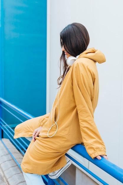 Jeune femme assise sur une balustrade bleue métallique portant un casque sur son cou Photo gratuit