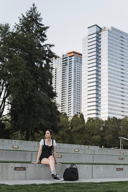 Jeune femme assise et bâtiments sur fond Photo gratuit