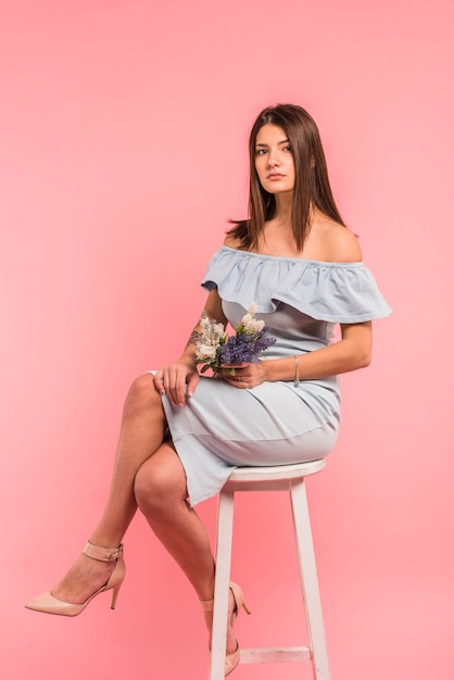 Jeune femme assise avec bouquet de fleurs sur une chaise Photo gratuit