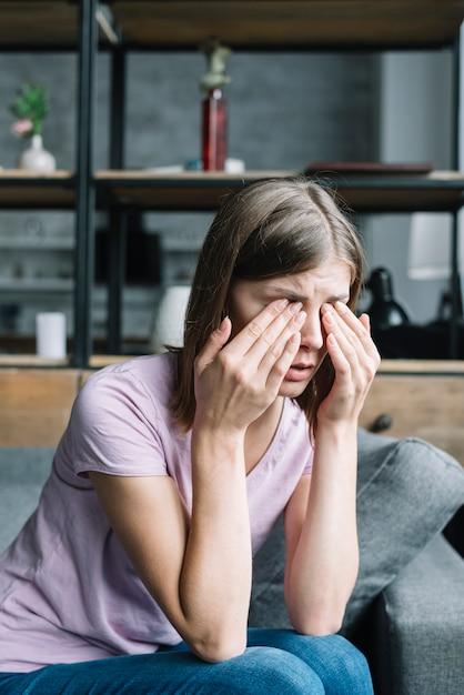 Jeune Femme Assise Sur Un Canapé Ayant Des Douleurs Aux Yeux Photo Premium