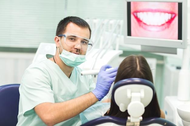 Jeune Femme Assise Sur La Chaise Du Dentiste Avec La Bouche Ouverte Au Bureau Du Dentiste Pendant L'examen. Photo Premium