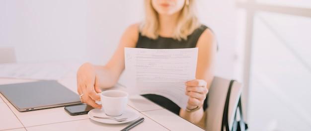 Jeune femme assise sur une chaise lisant le document buvant du café sur le lieu de travail Photo gratuit