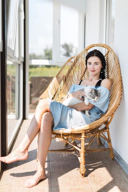 Jeune femme assise avec un chat sur une chaise en bois au patio Photo gratuit