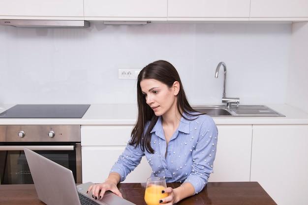 Jeune femme assise dans la cuisine tenant un verre de jus à l'aide d'un ordinateur portable Photo gratuit