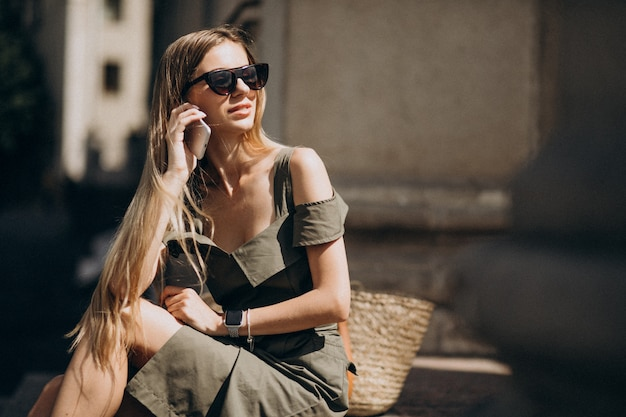 Jeune femme assise dans les escaliers et parlant au téléphone Photo gratuit