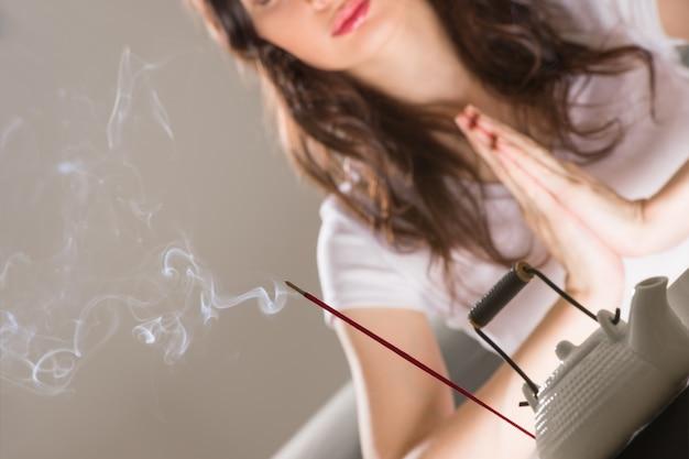 Jeune femme assise dans la méditation pose devant l'ensemble de thé et des bâtonnets d'arôme. concept de relaxation Photo Premium