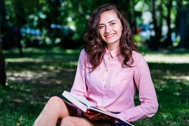 Jeune femme assise dans le parc avec un livre Photo gratuit