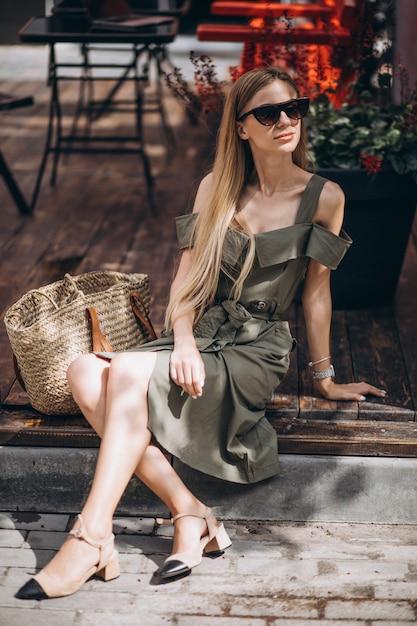 Jeune femme assise à l'extérieur du café Photo gratuit
