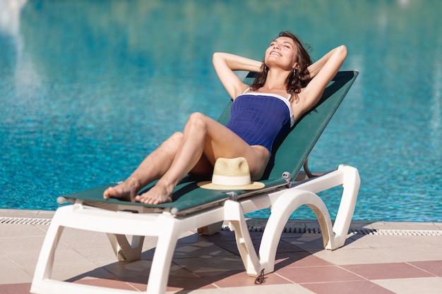 Jeune femme assise sur un lit de bronzage au bord de la piscine Photo gratuit