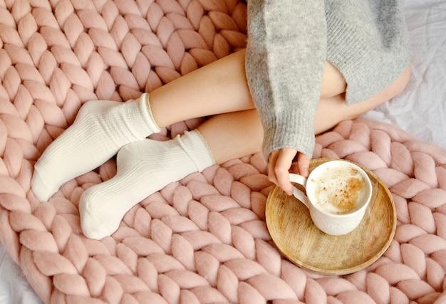 Jeune femme assise sur le lit avec une couverture à carreaux en laine de mérinos géante rose avec une tasse de cappuccino. Photo Premium