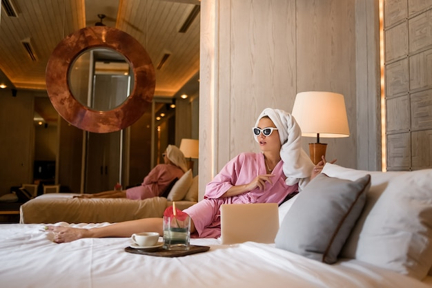 Jeune femme assise sur le lit dans un intérieur moderne avec son ordinateur portable et travaillant. design moderne pour chambre à coucher. détente après les journées de travail. Photo Premium