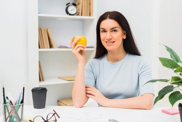 Jeune femme assise à la pomme au bureau Photo gratuit