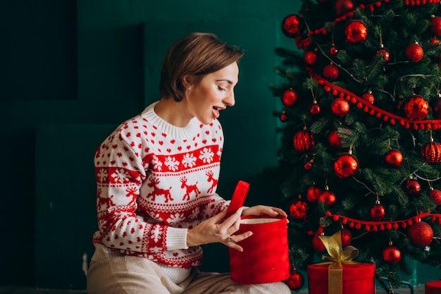 Jeune femme assise près du sapin de noël avec des boîtes rouges Photo gratuit