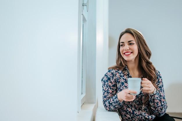 Jeune femme assise près de la fenêtre ayant une boisson chaude. rêverie. Photo Premium