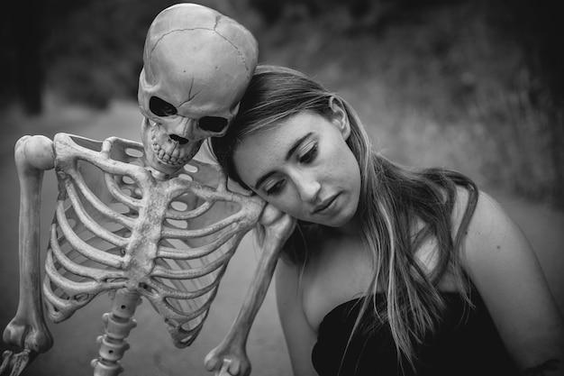 Jeune femme assise sur la route avec un squelette et regardant vers le bas Photo gratuit