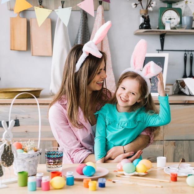 Jeune femme assise avec sa fille dans les oreilles de lapin près des oeufs de pâques Photo gratuit