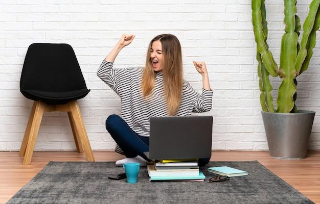Jeune femme assise sur le sol avec son ordinateur portable célébrant une victoire Photo Premium