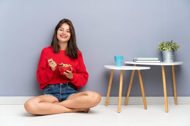 Jeune femme assise sur le sol et tenant un bol de céréales Photo Premium