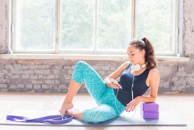 Jeune femme assise sur un tapis d'exercice à l'aide de smartphone Photo gratuit