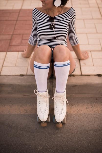 Jeune femme assise sur le trottoir avec patins à roulettes Photo gratuit