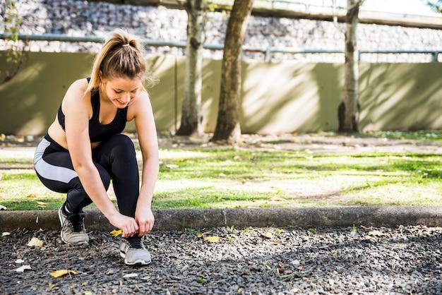 Jeune femme attachant ses baskets Photo gratuit